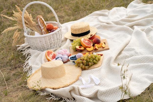 Pique-nique d'été élégant sur une couverture blanche.