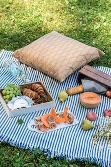 Pique-nique d'été sur l'herbe, jambon au melon, raisin, boulangerie, fruits
