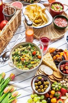 Pique-nique d'été avec salade de pâtes et planche à collation