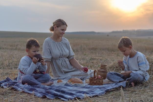 Pique-nique en famille dans la nature un soir d'été. mère et fils mangent du pain, du lait et des fruits sur un champ de blé en pente
