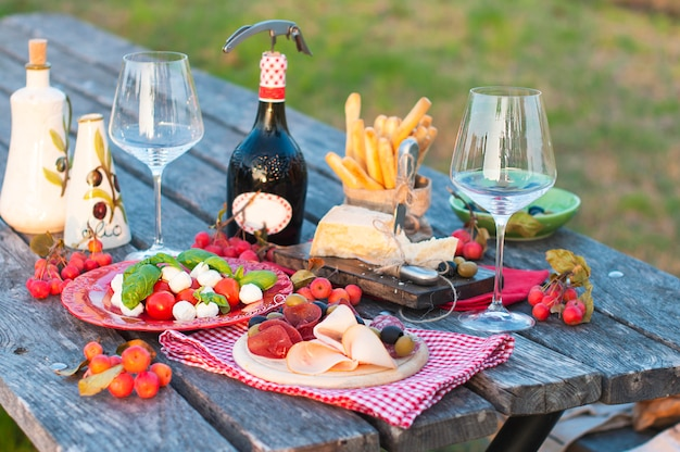Pique-nique italien avec vin rouge, parmesan, jambon et olives. déjeuner en plein air. collations traditionnelles. espace copie