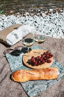 Pique-nique sur la plage avec deux verres à vin blanc bouteille de fromage baguette et raisin