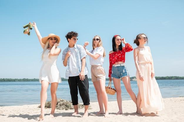 Pique-nique sur la plage jeune brillant festin saisonnier à la station balnéaire groupe d'amis célébrant