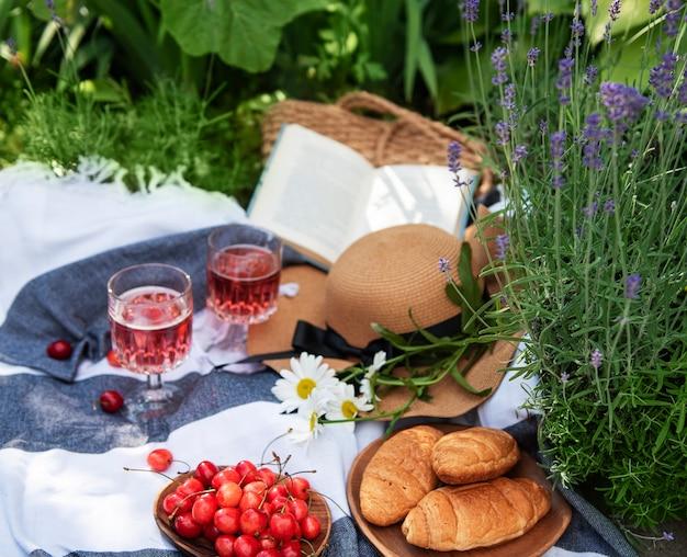 Pique-nique en plein air dans les champs de lavande. vin rosé dans un verre, cerises et chapeau de paille sur couverture