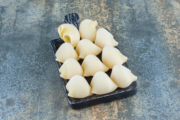 Piquer les pâtes dans le plateau, sur le fond de marbre.