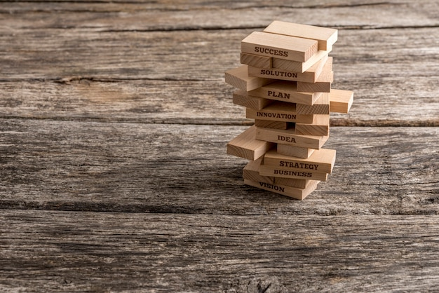 Des piquets en bois sont construits dans une tour et certains d'entre eux lisent des mots qui représentent les éléments les plus importants sur la voie du succès en affaires - vision, stratégie, idée, innovation, plan et solution.
