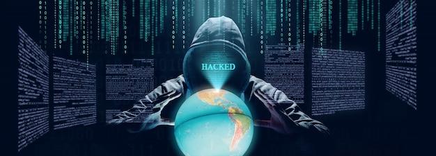 Un pirate imprime un code sur le clavier d'un ordinateur portable pour s'introduire dans un cyberespace