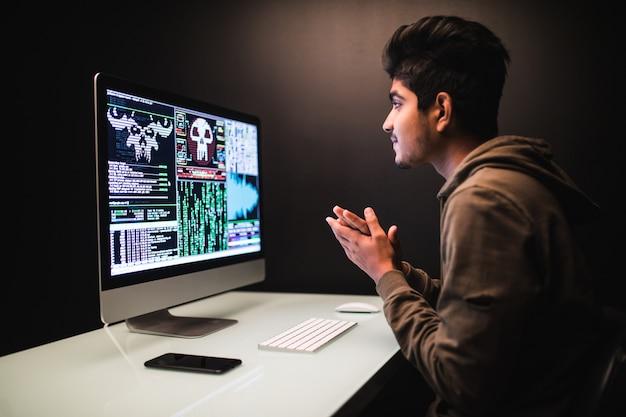 Pirate indien utilisant des ordinateurs pour voler des données sur un bureau sombre
