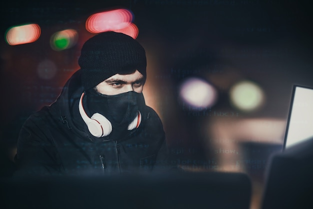 Un pirate informatique en colère portait une cagoule volant des données d'un ordinateur portable devant un fond noir et une lumière bleue. portrait rapproché. concept de piratage