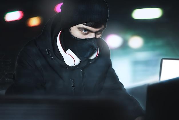Un pirate informatique en colère portait une cagoule volant des données via un pc depuis son repaire souterrain devant un fond noir et une lumière bleue. portrait rapproché. concept de piratage