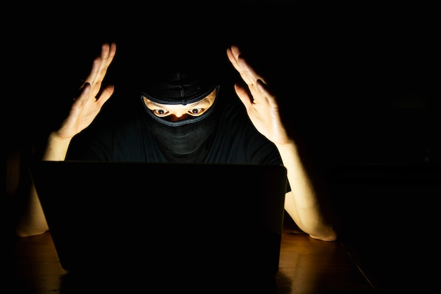 Pirate informatique faisant son travail avec un ordinateur portable dans la pièce sombre