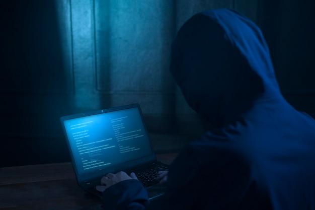Un pirate informatique utilise un ordinateur portable pour voler des données dans la nuit