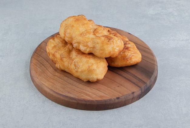 Piroshki au four avec pommes de terre sur planche de bois.