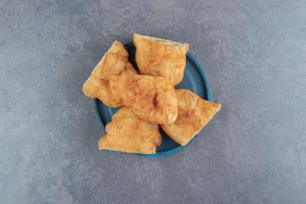 Piroshki tranché avec pommes de terre sur plaque bleue.