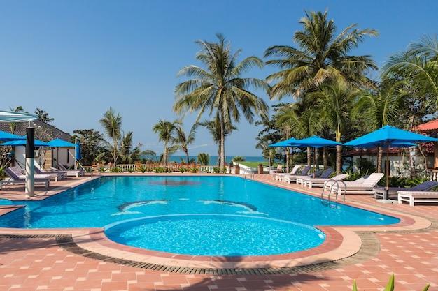 Piscine aux eaux bleues dans un complexe tropical avec palmiers