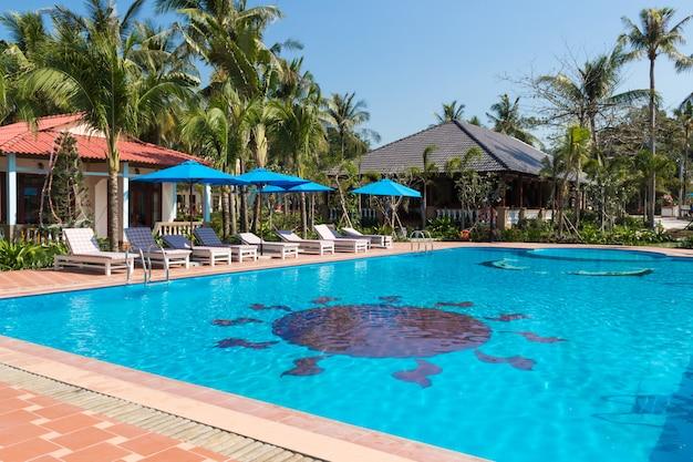 Piscine dans un complexe tropical avec des palmiers