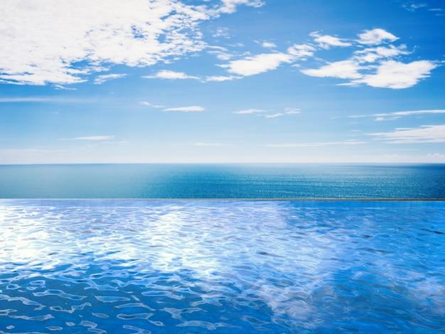 Piscine à débordement avec mer bleue et ciel bleu
