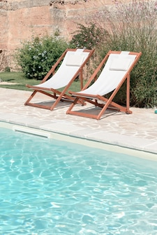 Piscine avec eau bleu clair et deux chaises longues par beau temps dans une cour