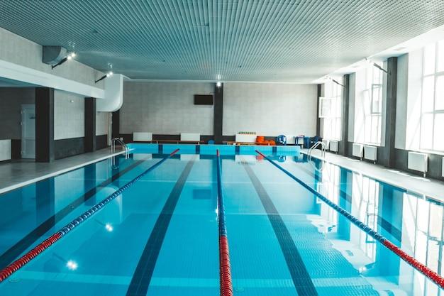 Une piscine d'eau avec de l'eau claire bleue transparente, sur laquelle brille la lumière du soleil