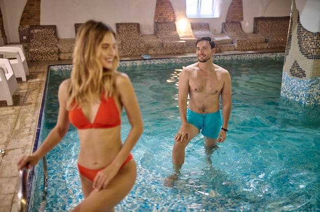 Piscine. une jolie jeune femme et son petit ami passent du temps dans une piscine au centre de spa