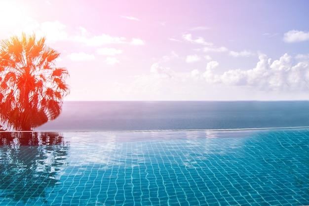 Piscine avec vue sur la mer bleue et fond de ciel bleu