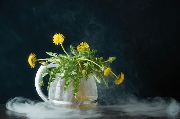 Pissenlit avec des racines et des feuilles dans une théière en verre