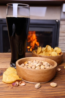 Pistache, chips et bière sur fond de cheminée en feu