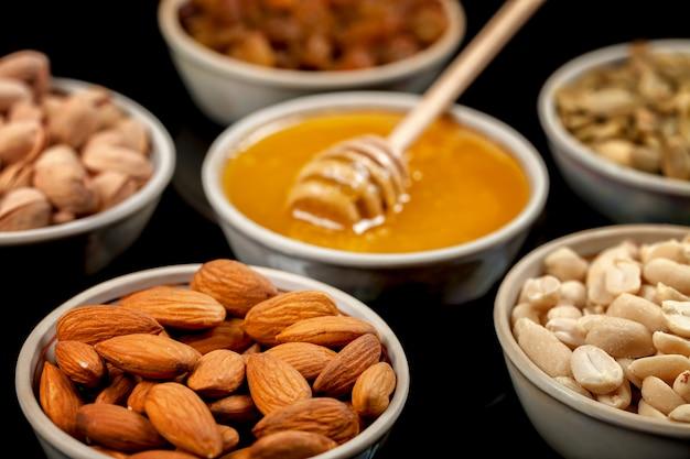 Pistaches, amandes, arachides, graines de citrouille, raisins secs et miel dans des assiettes en céramique.