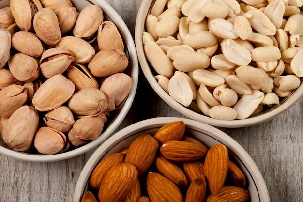 Pistaches, amandes, cacahuètes dans des assiettes en céramique. sur la table en bois