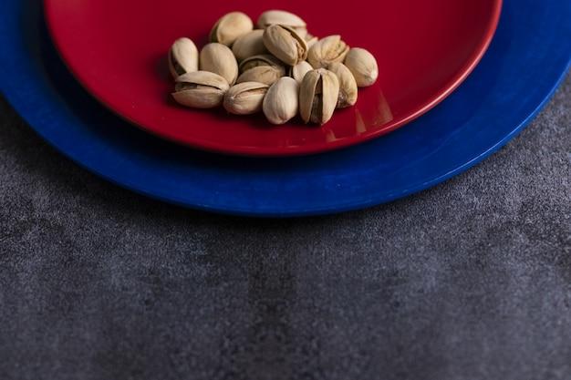 Pistaches crues biologiques présentées sur une plaque rouge et bleue