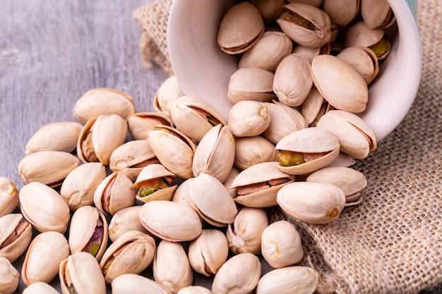 Les pistaches dans un bol en céramique blanche sur une table en bois.