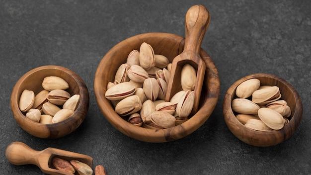 Les pistaches dans des bols avec des cuillères en bois