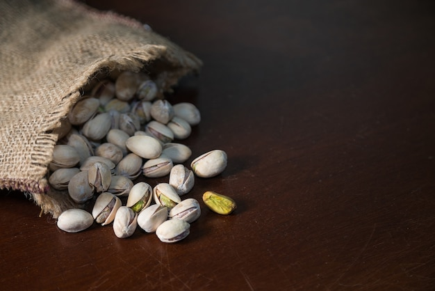 Les pistaches dans un sac en lin sur table en bois