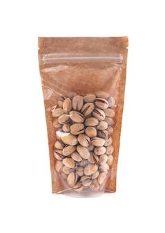 Pistaches dans un sac en papier brun. doy-pack avec fenêtre en plastique pour produits en vrac. fermer. fond blanc. isolé.