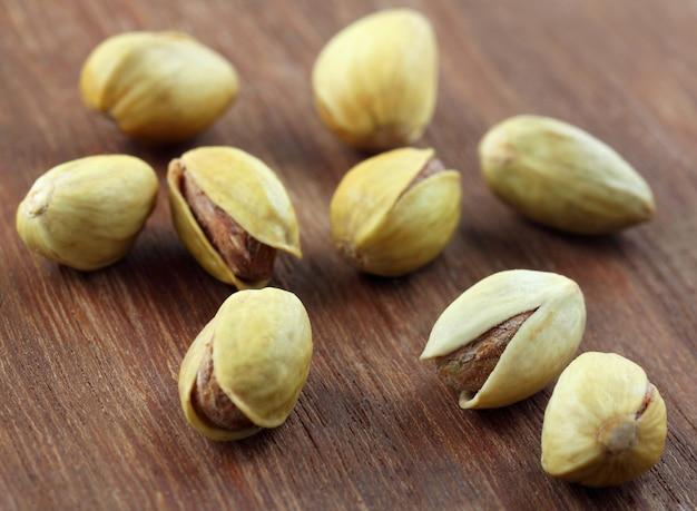 Les pistaches se bouchent sur une surface en bois texturée