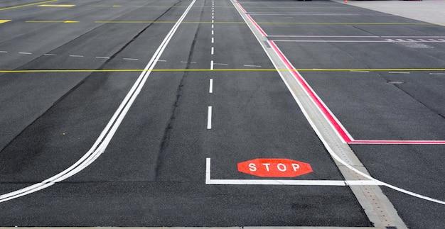 Piste d'aérodrome et voie de circulation avec marquage et panneaux.