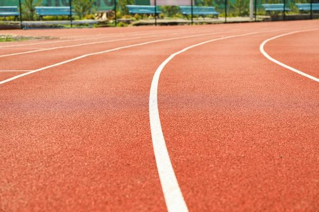 Piste de course rouge avec des lignes blanches en plein air, espace copie