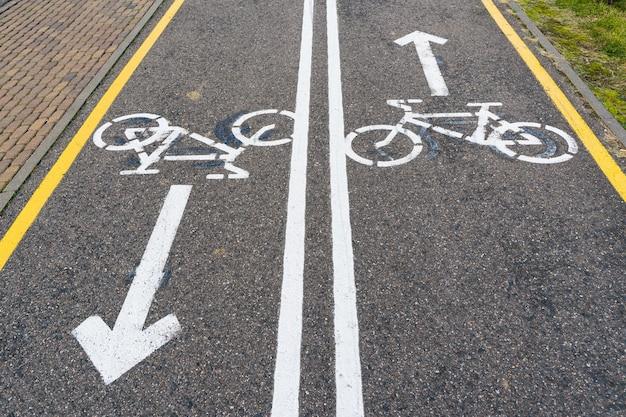 Piste cyclable bidirectionnelle avec panneaux de vélo et flèches peintes sur asphalte.