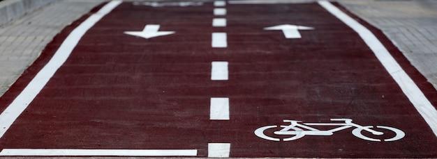 Une piste cyclable blanche signe sur une surface asphaltée de la route de la ville dans la zone de sécurité à vélo de premier plan