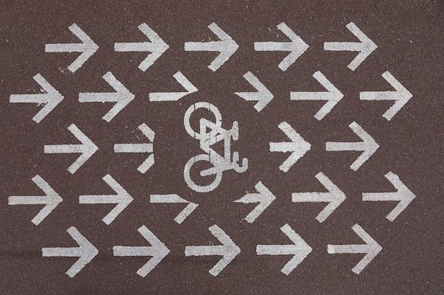 Piste cyclable de marquage routier avec des flèches pointant vers la droite sur l'asphalte gris