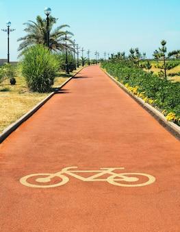 Piste cyclable rouge ou chemin avec signe de vélo au jour d'été ensoleillé