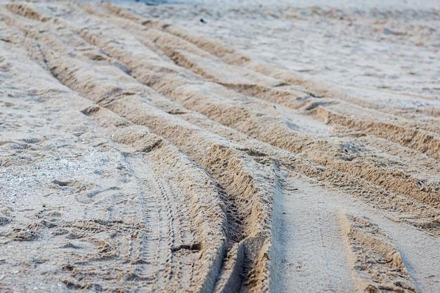 Piste de roue sur la plage de sable.