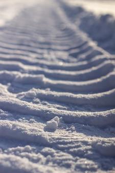 Pistes fraîches du tracteur dans la neige en hiver. déneigement