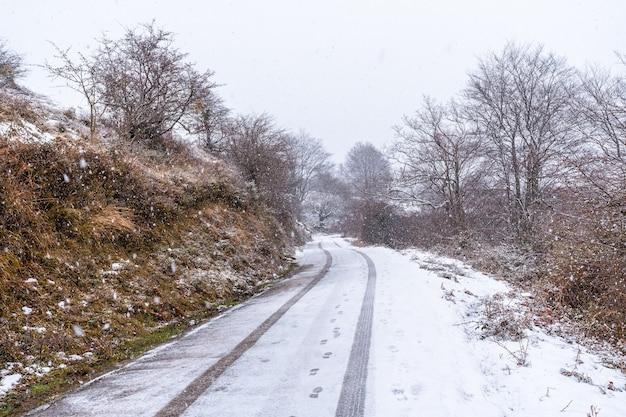 Pistes de voitures sur la route du mont aizkorri à gipuzkoa. paysage enneigé par les neiges d'hiver