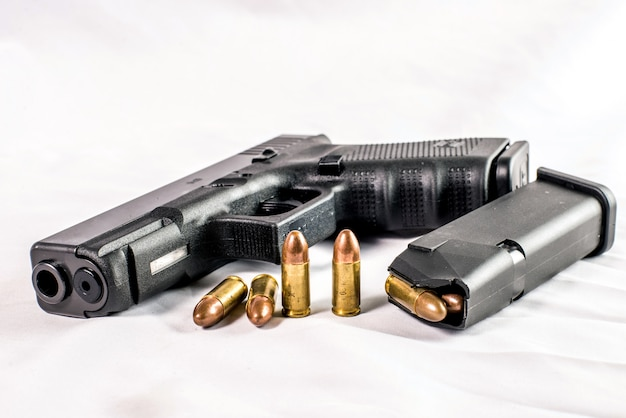Pistolet 9 mm et balles parsemées de munitions sur fond en bois