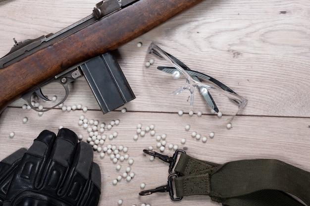 Pistolet airsoft avec des lunettes de protection et beaucoup de balles