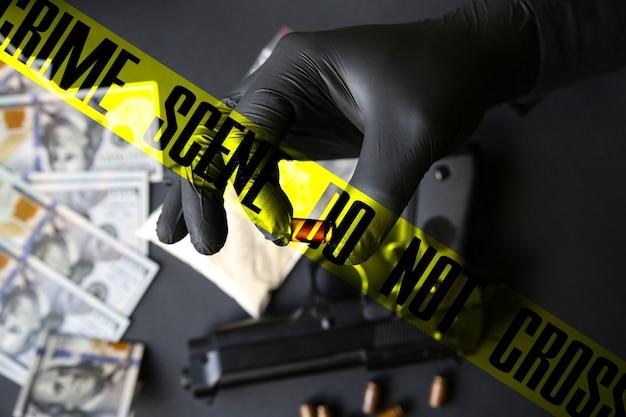 Pistolet allongé sur la table. homme en gants noirs tenant des balles. vente de drogue illégale. la scène de crime ne traverse pas la bande. dollars.