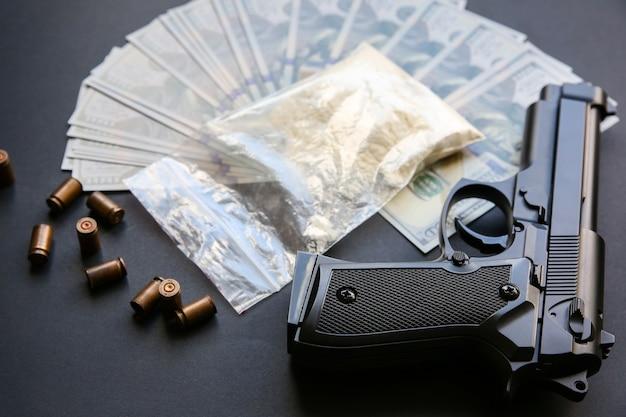 Pistolet à balles posé sur la table. problèmes criminels. drogues et argent sur fond noir. vente illégale.