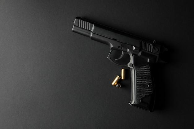 Pistolet et balles traumatisantes sur fond noir. arme d'autodéfense