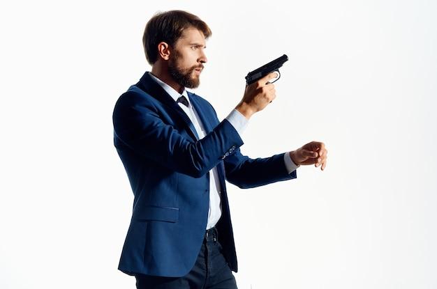 Pistolet d'homme dans les mains de l'agent des émotions de la mafia fond clair